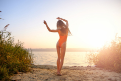 Attractive girl in swimsuit on the beach at sunrise